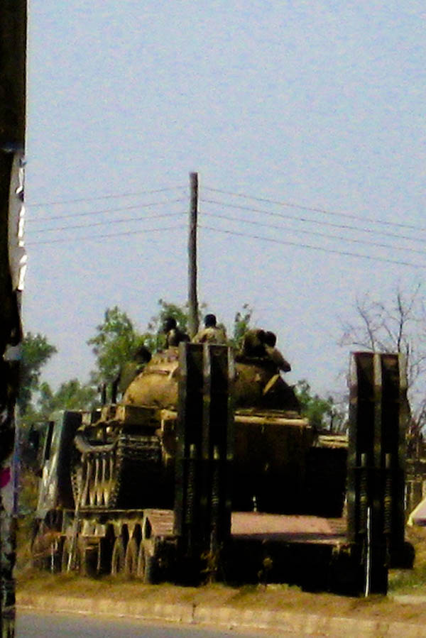 Young SPLA soldiers ride through Juba atop a tank on a flatbed truck