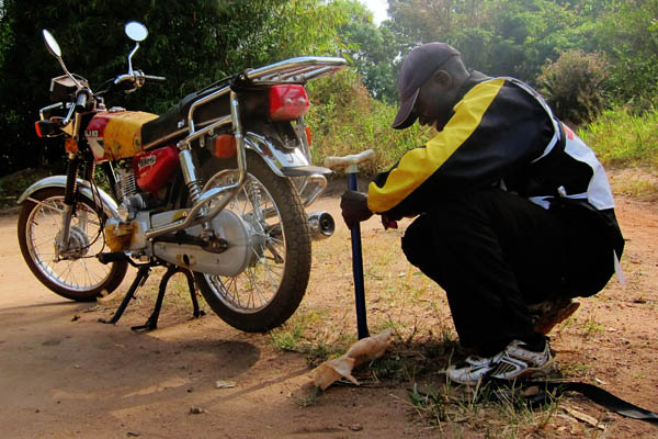 Inflating a flat motorcycle tire outside Ndedu, DR Congo
