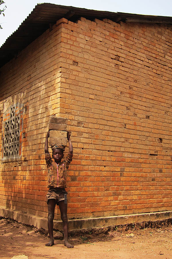Child carrying bricks, Duru, DR Congo