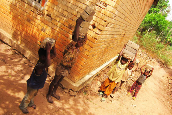 Children carrying bricks, Duru, DR Congo