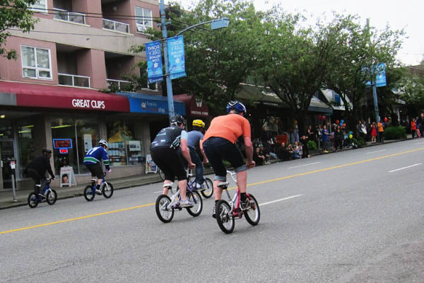 Adults on toddler bicycles on West 10th Avenue, Vancouver