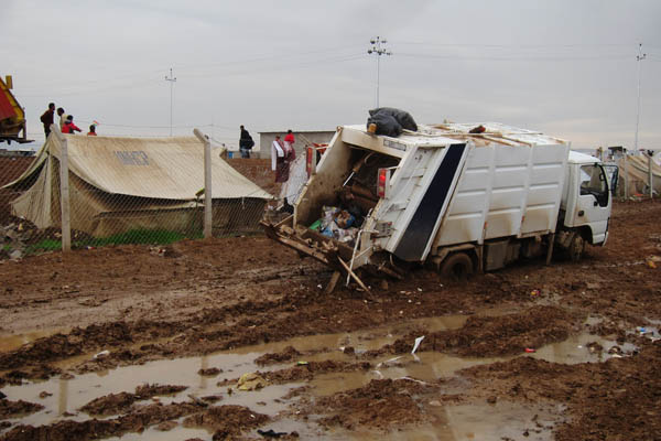 Garbage truck stuck in mud in Domiz Refugee Camp for Syrians, Iraq