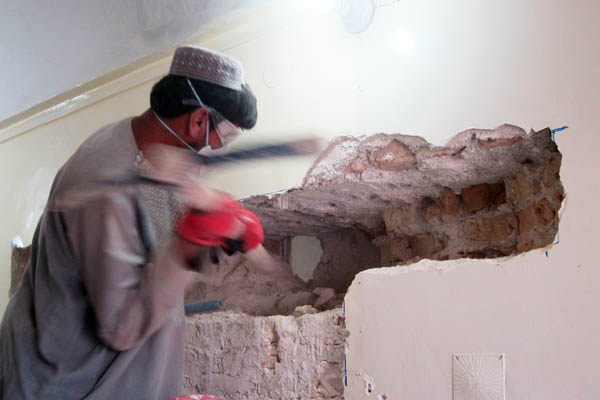 Using a pick-axe to break through a 60cm-thick wall in Bost Provincial Hospital, Helmand