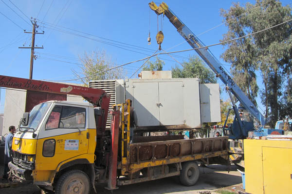 A crane lifts an old generator onto a flatbed truck at Bost Hospital