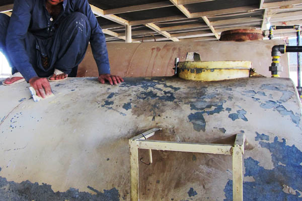 Scraping old paint off a diesel fuel storage tank