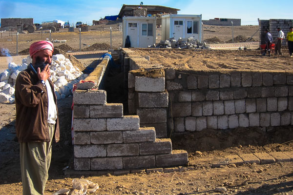 A member of the Yazidi construction team takes a smoke break from building the foundation of the new health centre in Domiz Refugee Camp