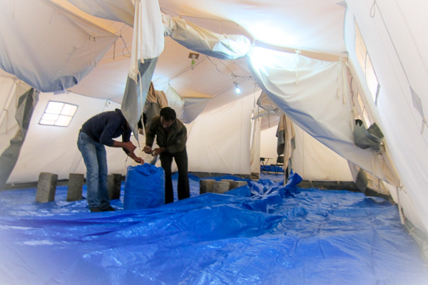 Placing cement breezeblocks to weigh down the tents during a building wind storm