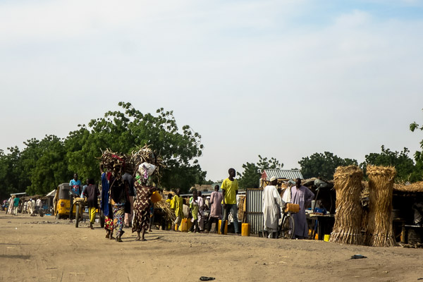 Women carrying wood, woven thatch mats for sale by the roadside in Monguno, Borno State, Nigeria